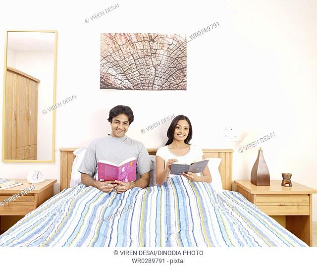 Young man and woman holding novels sitting on bed MR702V,702U