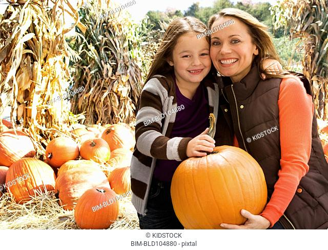 Caucasian mother and daughter holding pumpkin