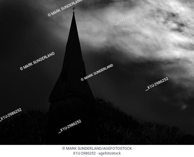 Silhouette of a Church Spire against a Dark Cloudy Sky. North Yorkshire, England
