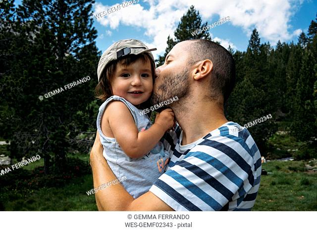 Spain, Father hugging and kissing his little daughter in nature