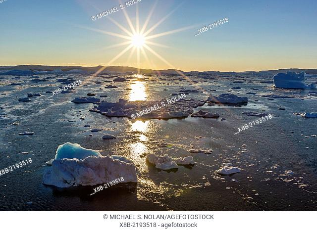 Sunset over icebergs calved from the Ilulissat Glacier, a UNESCO World Heritage Site, Ilulissat, Greenland