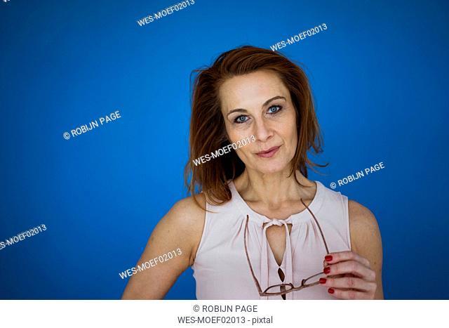 Redheaded businesswoman holding glasses, portrait