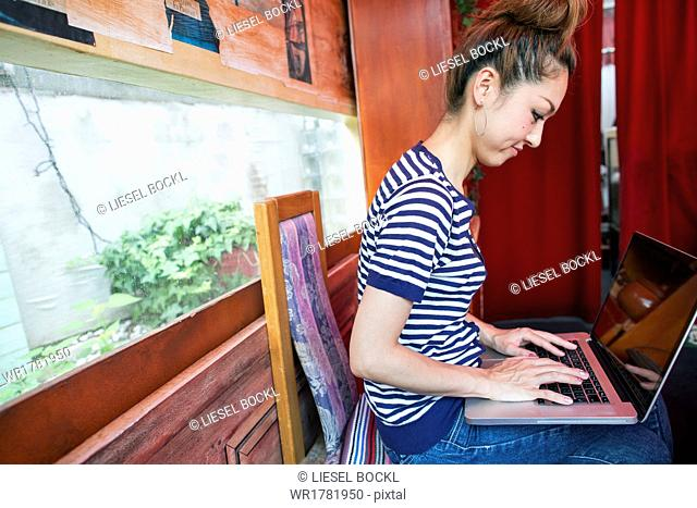 A woman working on a laptop and sitting indoors