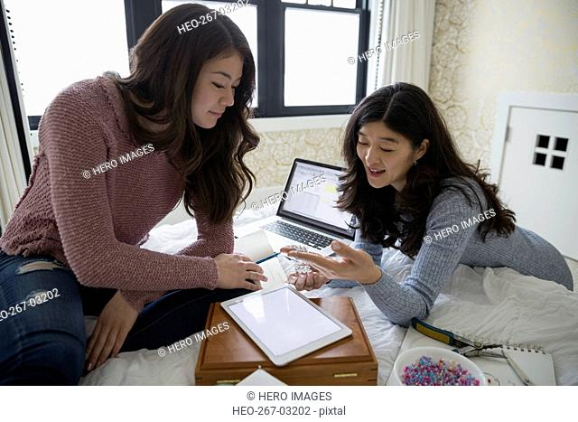 Mother and teenage daughter making jewelry on bed