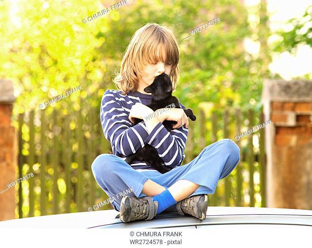 Boy Sitting Holding a Pet Kitten