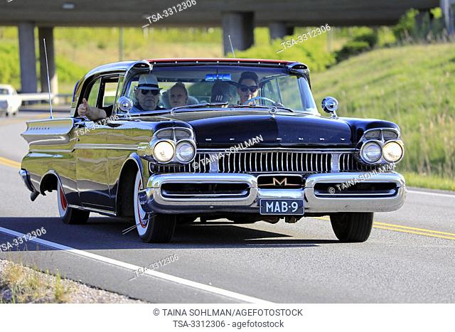 Salo, Finland. May 18, 2019. Family driving a late 1950s classic black Mercury car along highway on the popular event Salon Maisema Cruising 2019