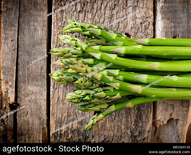 Fresh organic green asparagus on a rustic wooden kitchen table, healthy food concept