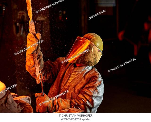 Industry, worker at furnace during melting copper, wearing a fire proximity suit