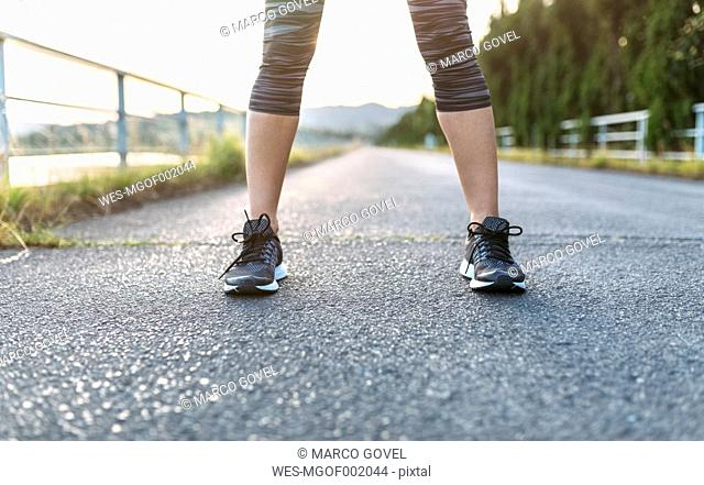 Woman standing on road preparing for training