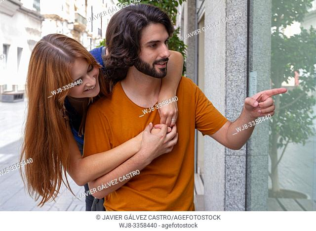 Portraits of a couple Young, accomplices and smiling looking at shop windows