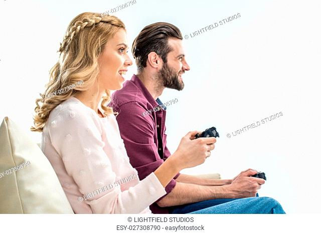 Smiling young couple sitting on couch and playing video games with joysticks