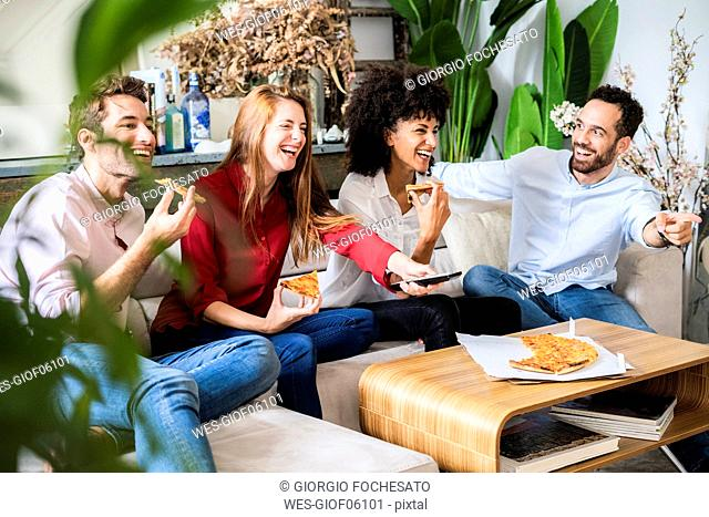 Friends having fun, eating pizza, watching TV