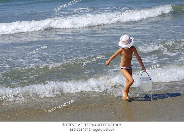 A young girls play on the Mediterranean beach of Grau d'Agde, France