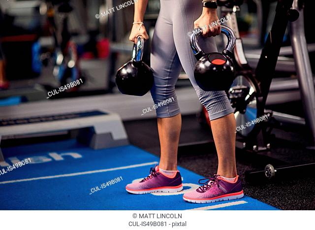 Waist down view of young woman holding kettle bells in gym