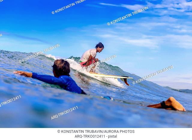 Man swimming beside surfer riding small wave, Kuta, Lombok, Indonesia