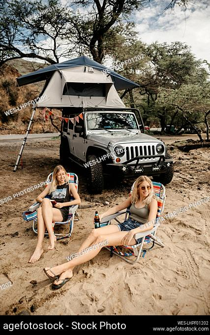 Friends relaxing on deck chairs against SUV, USA, Hawaii, Maui