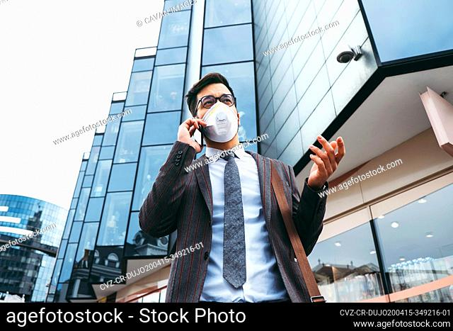 Business man with protective face mask using phone on city street