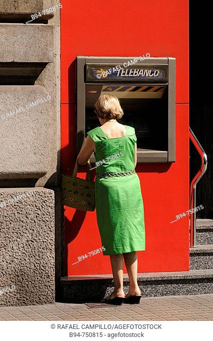 Woman using ATM, Barcelona. Catalonia, Spain