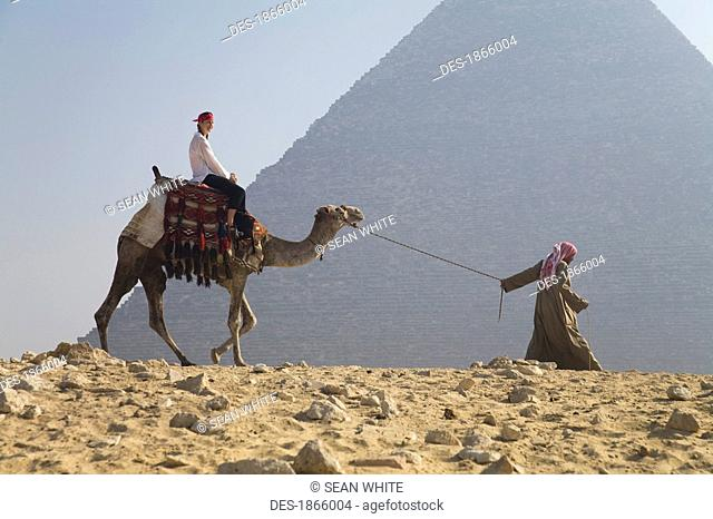 Young woman tourist riding a camel lead by a guide at the Pyramids of Giza, Egypt