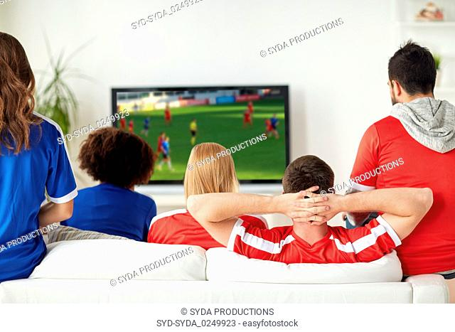 friends or soccer fans watching game on tv at home