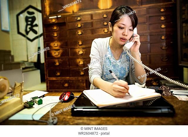 A small artisan producer of specialist treats, sweets called wagashi. A woman taking an order over the telephone and writing with a pen
