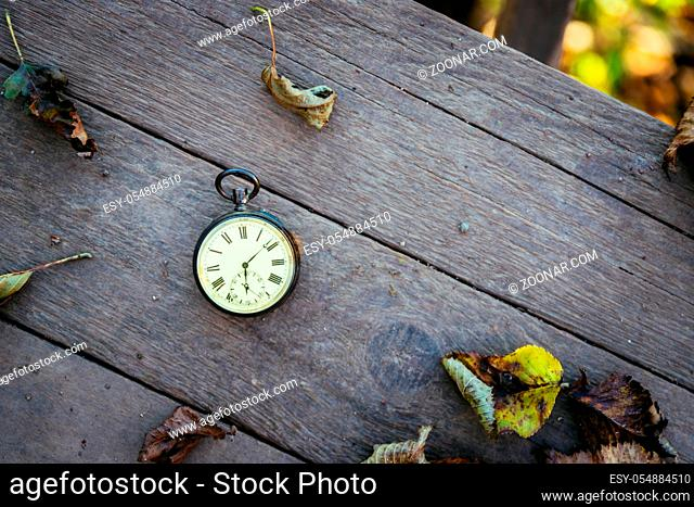 Vintage pocket watch on a wood board, colourful leaves, autumn
