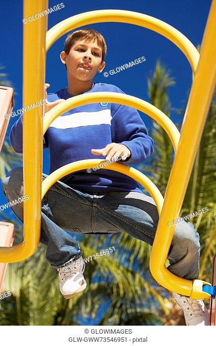 Low angle view of a teenage boy sitting on a jungle gym
