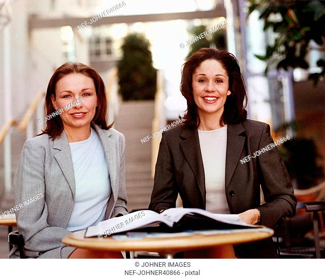 Portrait of two business women at a table