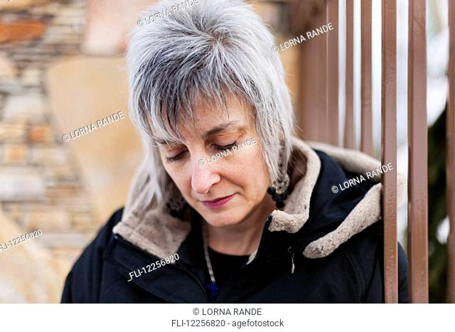 Grey-haired woman with fashionable haircut looking down; Langley, British Columbia, Canada