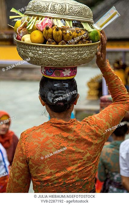 Balinese woman carrying an offering basket inside Pura Tirta Empul, Bali, Indonesia