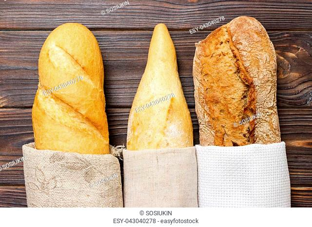 Loaf of bread in a bag european style on a rustic table