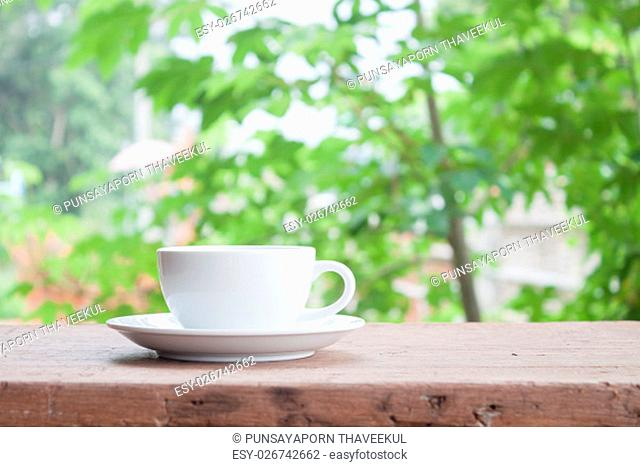 White coffee cup on tabletop with blurred green leaves background