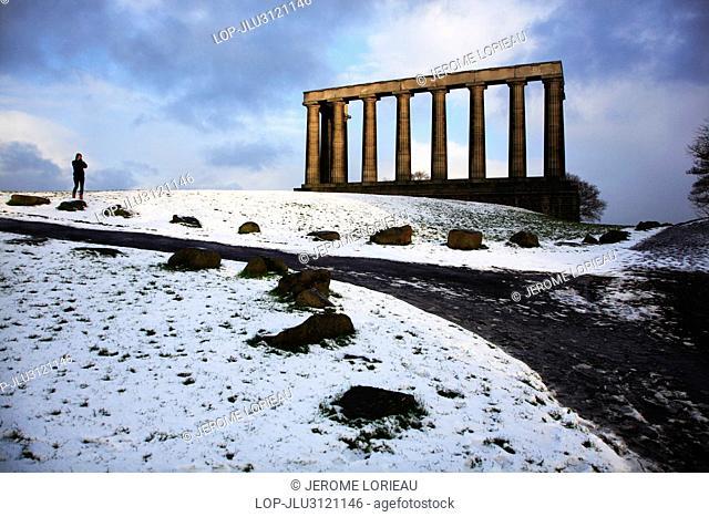 Scotland, City of Edinburgh, Edinburgh. A woman walking in the snow by the Scottish National Monument on Calton Hill