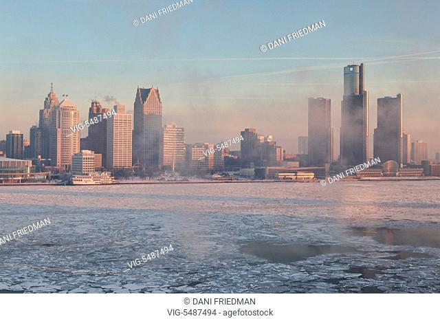 Smoke and fumes from nearby factories shrouds the skyline of downtown Detroit, Michigan, USA. Chunks of ice can be seen floating along the Detroit River