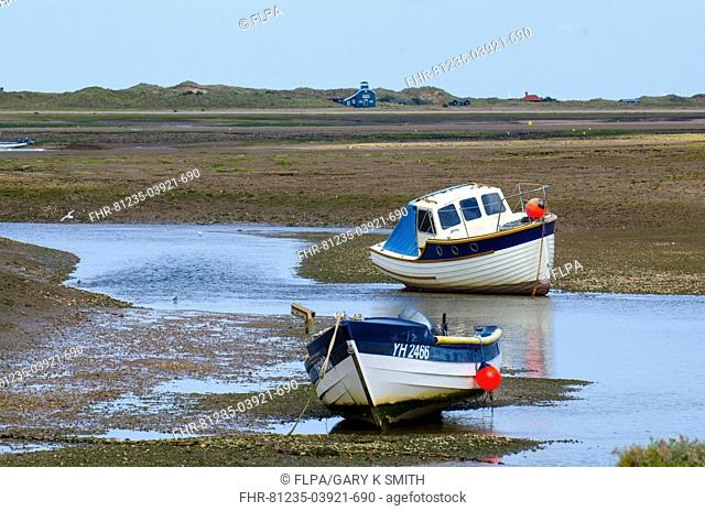 Pleasure boats in tidal coastal creek at low tide, with dunes and old lifeboat house visitor centre in distance, Blakeney Point, North Norfolk, England