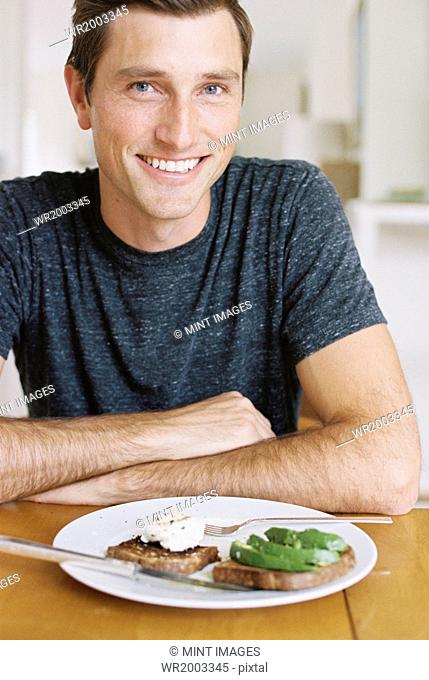 Man sitting in front of a plate of food at a table, looking at camera, smiling