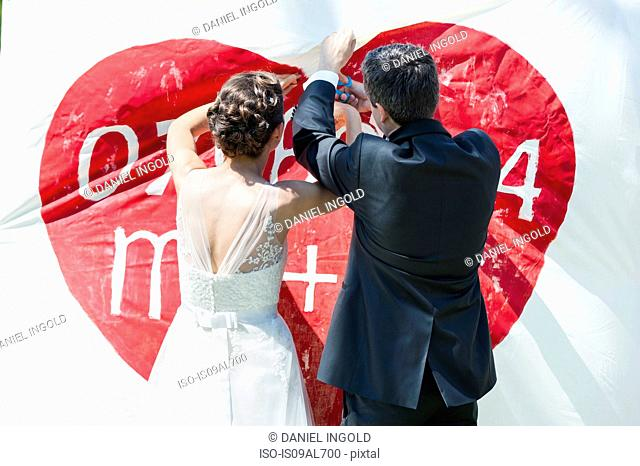 Rear view of bride and bridegroom hanging bespoke banner with red heart