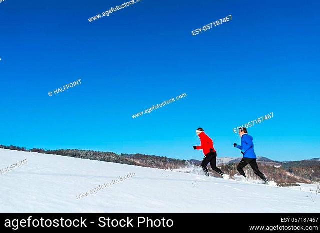 A side view of happy senior couple jogging in snowy winter nature. A copy space