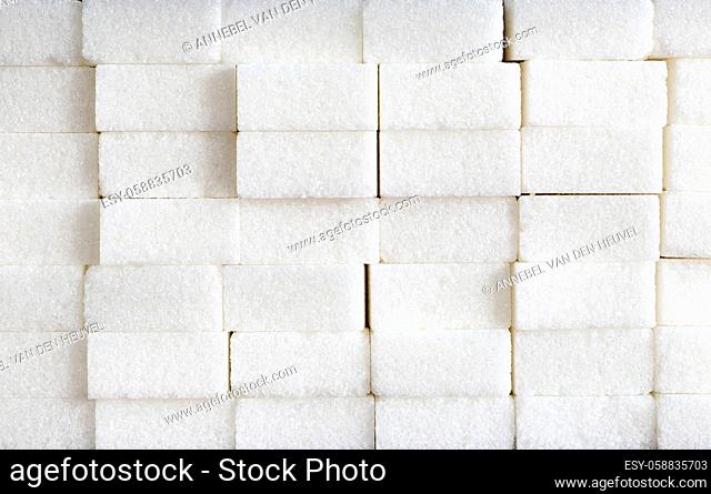 White sugar cubes composition of Brick wall, pile of sugar, unhealthy food, ingredient, candy and sweets closeup