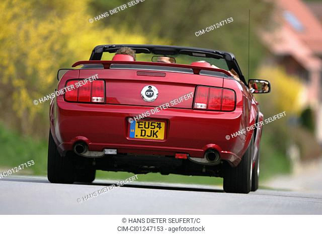 Car, Ford Mustang GT Convertible, model year 2005-, ruby colored, driving, diagonal from the back, rear view, country road, open top