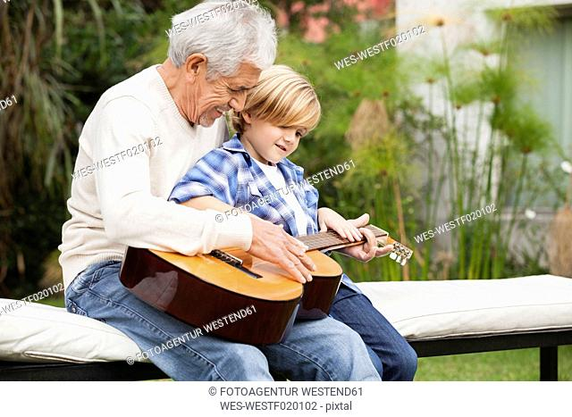 Grandfather and grandson with guitar outdoors