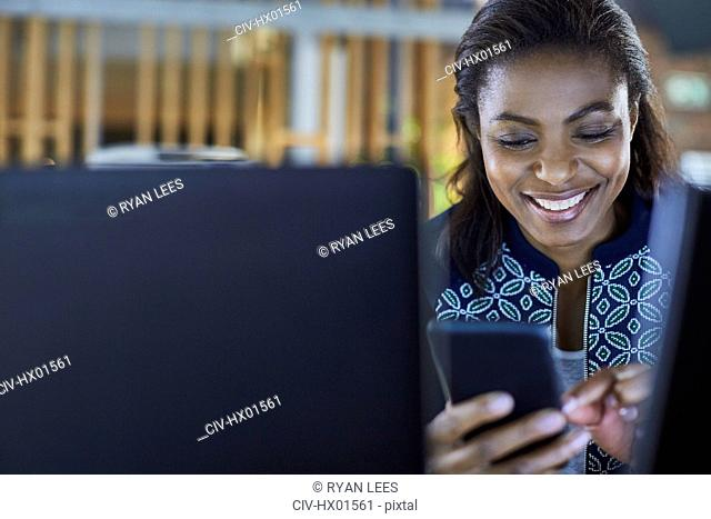 Smiling businesswoman texting with cell phone