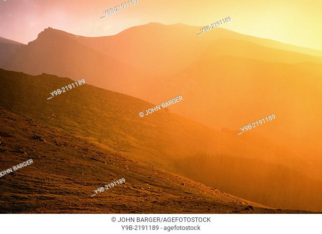 Rainclouds and fog turn orange at sunset, Mt. Evans Recreation Area, Arapaho National Forest, Colorado, USA