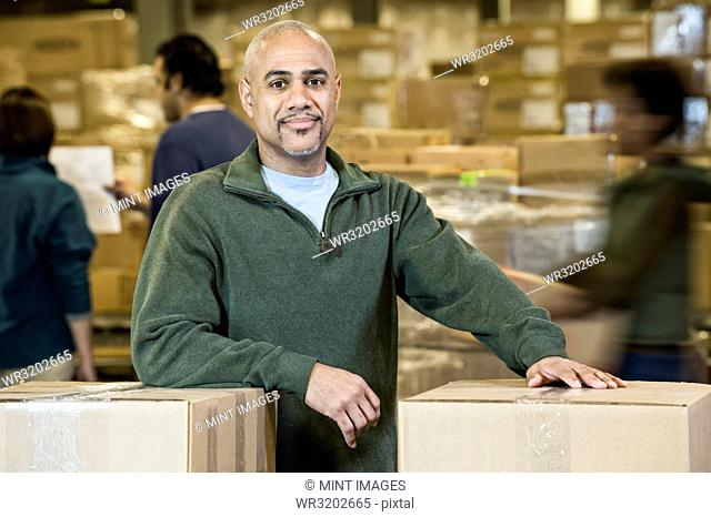 A portrait of a black warehouse business manager. surrounded by storage boxes and employees