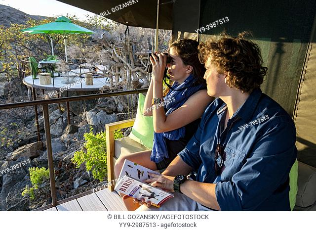 Couple birdwatching on balcony of tent at Huab Under Canvas, Damaraland, Namibia, Africa