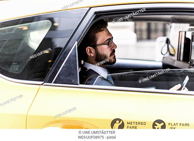 USA, New York City, businessman using cell phone in a taxi