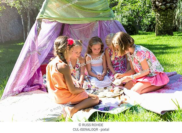 Five girls playing with toy tea set in front of teepee