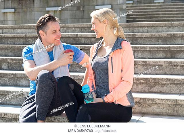 Couple in sportswear sitting on stairs, conversation, smiling, eye contact