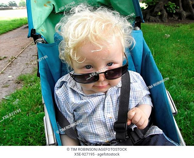 18 month boy sitting in pram wearing adult sunglasses, comical