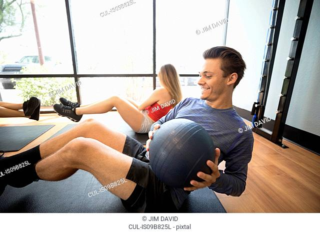 Friends training with medicine ball in gym